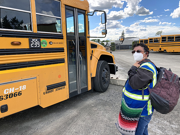 Molly in front of a yellow school bus with a mask on and her bags